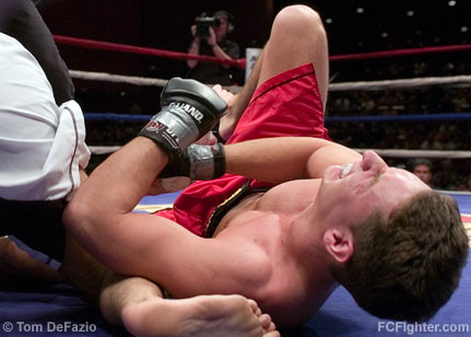 Ring of Combat 12: Bill Worfolk writhes in pain after being caught in an armbar by Joe Scarola - Photo by Tom DeFazio