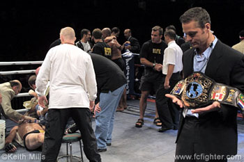 The aftermath.  Lutter attended to by doctor, Rivera in his corner in the middle, and promoter Tom Hafers holding the belt on the right.  UFC Pez Dana White is bending down with the black shirt and jeans in the middle of the ring talking to Lutter but his face is obscured by someone else.