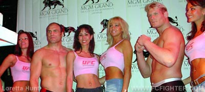 Randy Couture (left) and Josh Barnett pose with ring card girls
